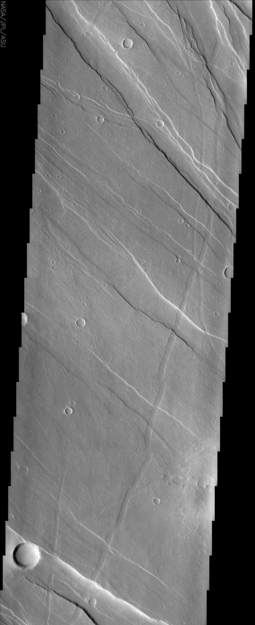 This image of Tharsis Rise from NASA's Mars Odyssey shows a series of linear features called graben, which are associated with crustal extension resulting in up and down blocks of crust that run perpendicular to the direction of the extension.
