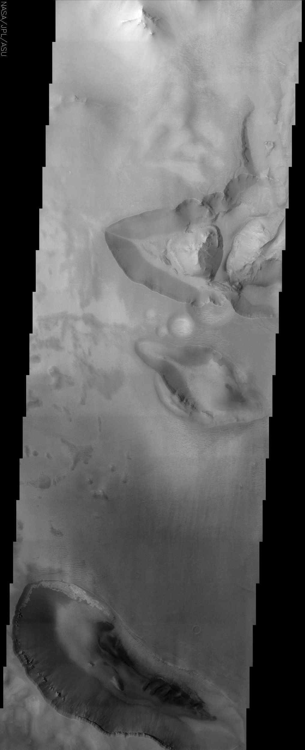 This NASA Mars Odyssey image shows the transition zone between maze-like troughs of Noctis Labyrinthus and the main Valles Marineris canyon system. This huge system of troughs near the equator of Mars was most likely created by tectonic forces.