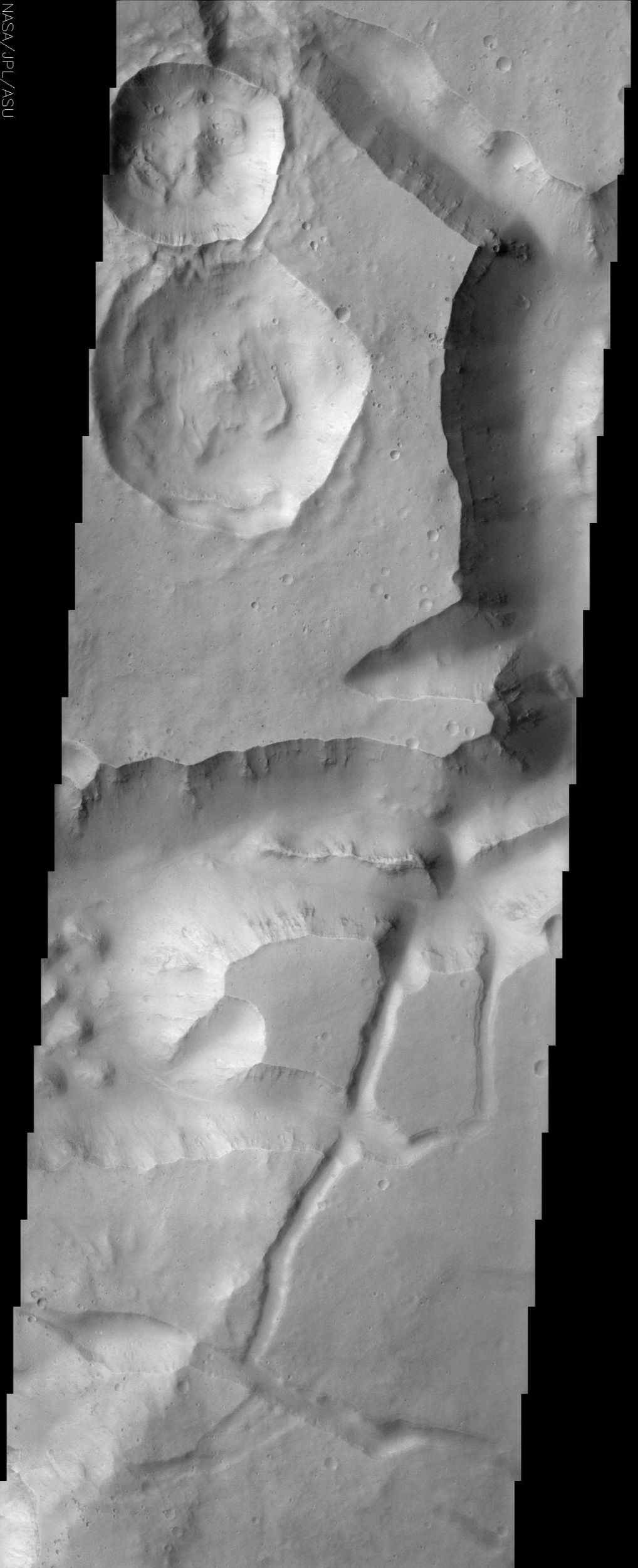 This image from NASA's Mars Odyssey shows a portion of Aureum Chaos located just south of the Martian equator. This fractured landscape contains canyons and mesas with two large impact craters in the upper left.