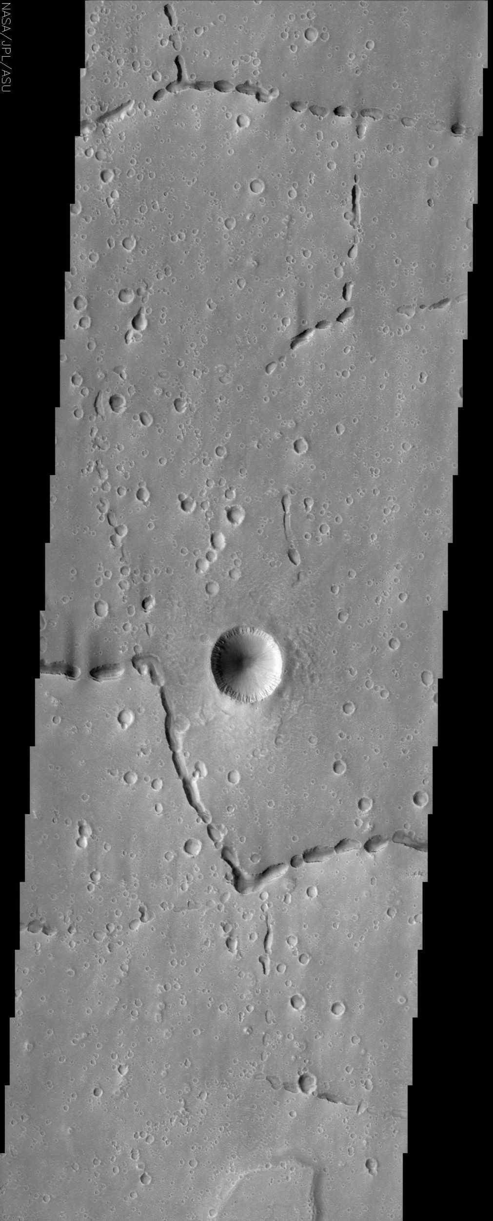 Off the western flank of Elysium are the Hephaestus Fossae, seen in this image from NASA's Mars Odyssey, with linear arrangements of small, round pits. These features are commonly called 'pit chains' and most likely represent the collapse of lava tubes.