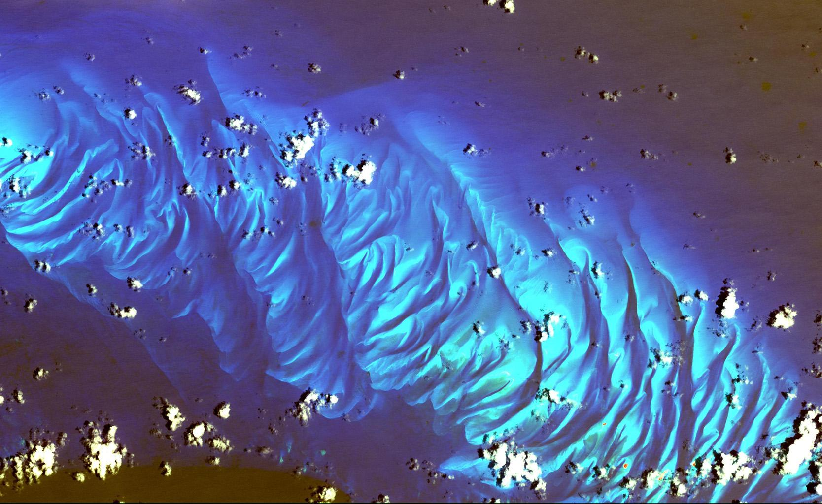 This image from NASA's Terra spacecraft shows features that look like folded material are carbonate sand dunes in the shallow waters of Tarpum Bay, southwest of Eleuthera Island in the Bahamas.