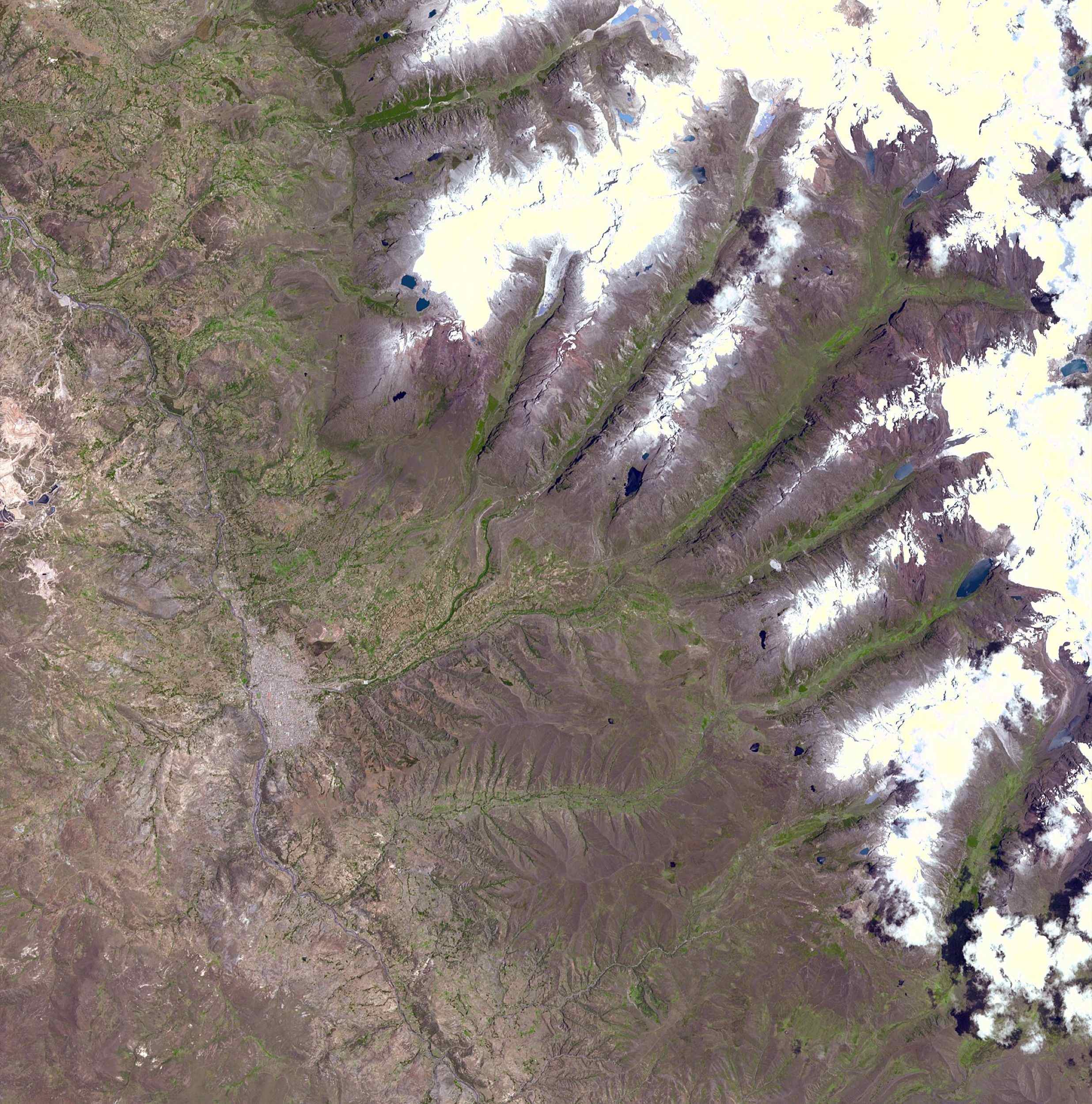 This image acquired by NASA's Terra spacecraft on November 5, 2001, shows a chunk of glacier was threatening to fall into an Andean lake and cause major flooding in Huraez, a Peruvian city of 60,000.