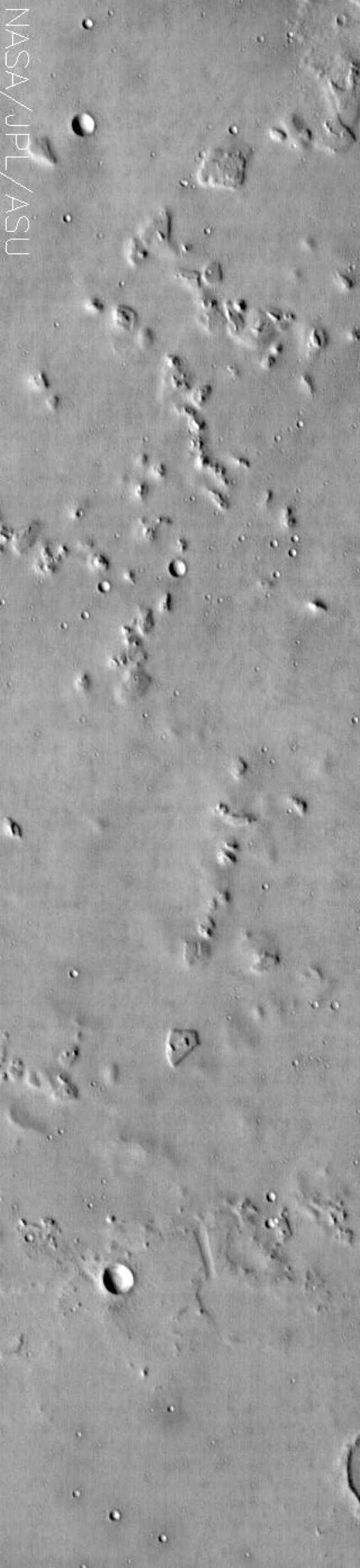 This NASA Mars Odyssey image shows a location near the highland-lowland boundary scarp in a region called Nepenthes Mensae with relatively smooth plains dotted with some craters and stepped mesas and knobs.