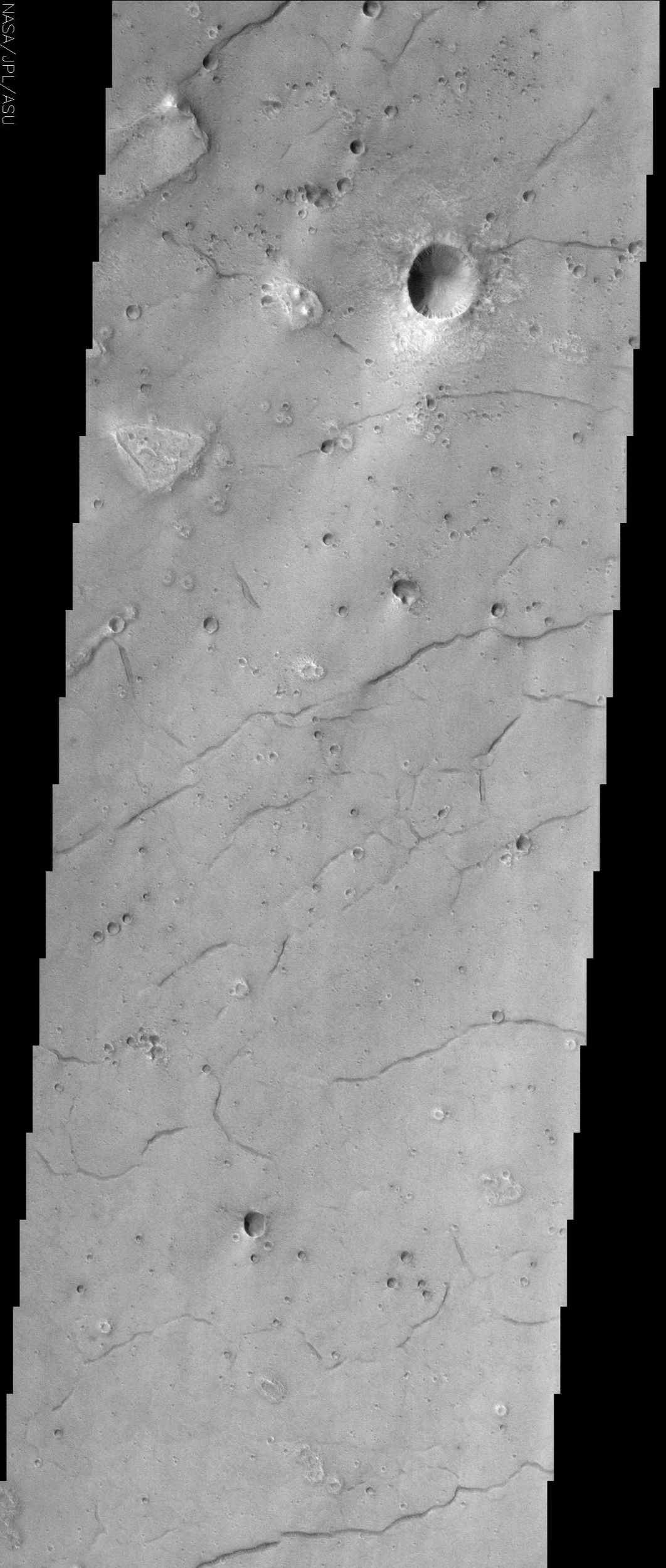 The lineations seen in this NASA Mars Odyssey image occur in Acidalia Planitia. These fissures, or cracks in the ground, are possibly evidence that there was once subsurface ice or water in the region.
