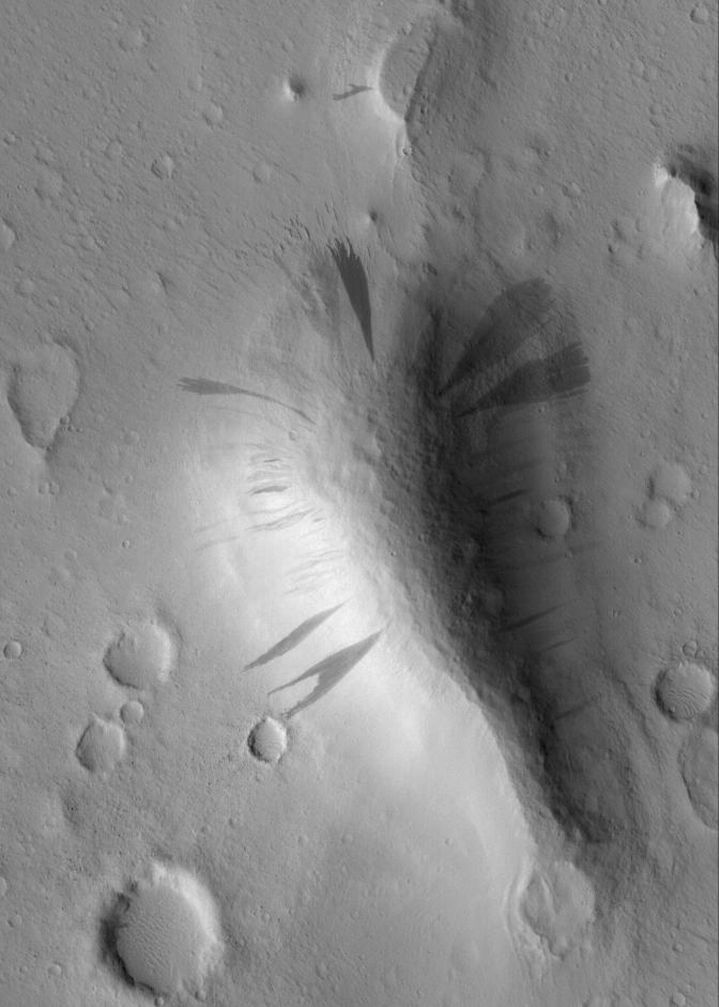 NASA's Mars Global Surveyor shows dark slope streaks coming down the slopes of a knob in western Amazonis Planitia on Mars. All of the surfaces are mantled by dust. On the slopes, mass movement of dry dust has created the streaks.