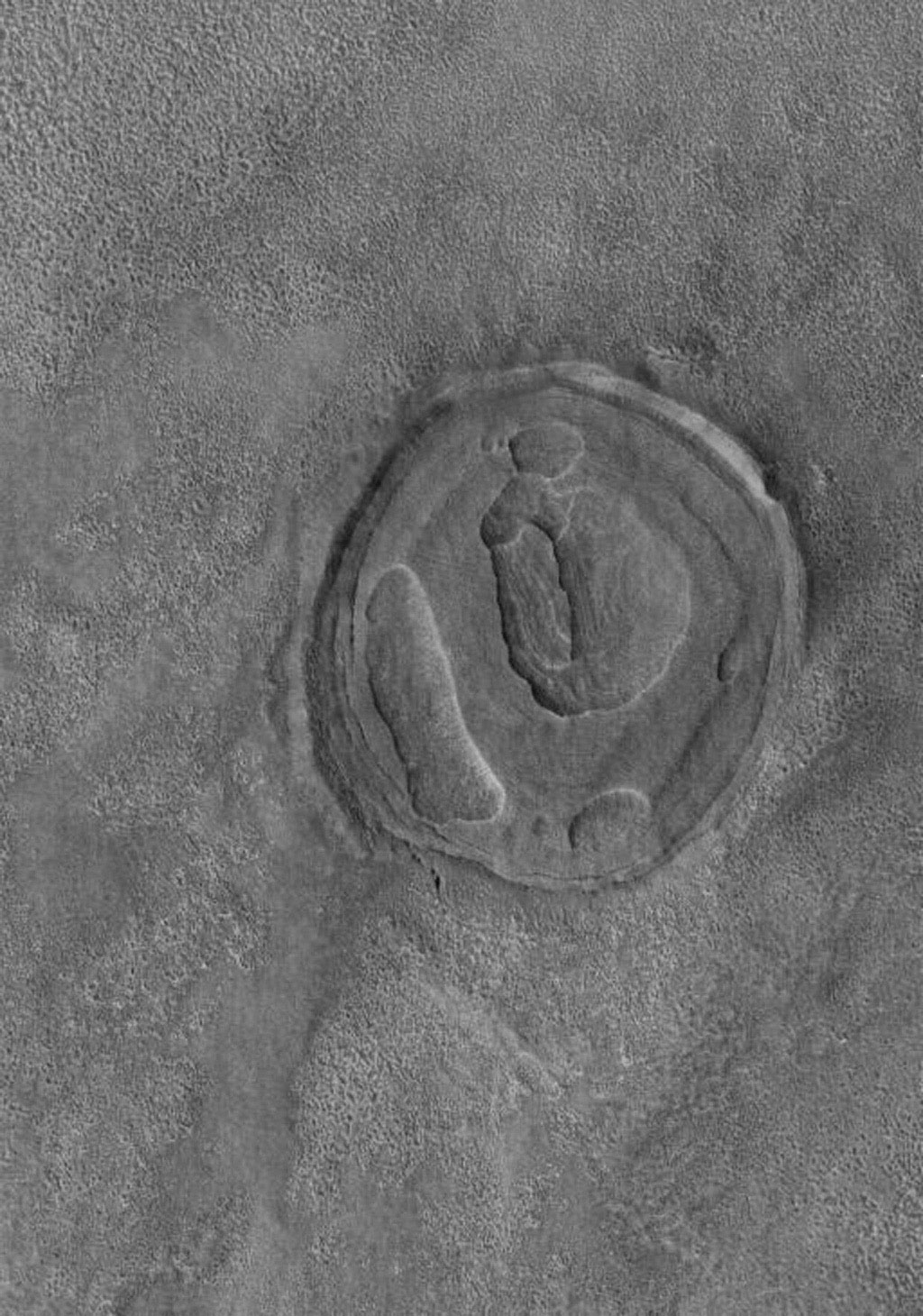 NASA's Mars Global Surveyor shows a circular feature on the martian northern plains. It was once a crater formed by meteoritic impact. It was completely filled and buried by and within layered material.
