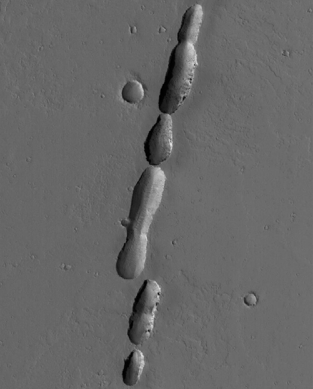 NASA's Mars Global Surveyor shows a chain of pits associated with dust-covered lava flows in northern Tharsis on Mars. The pits formed along a fault; some of the flows may have erupted along this same fault.