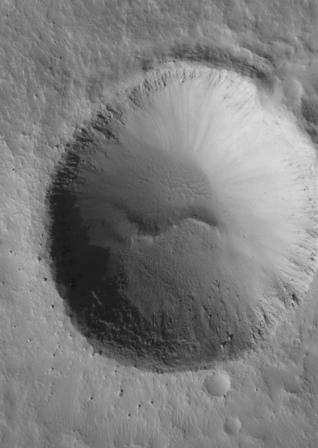 NASA's Mars Global Surveyor shows an impact crater with large boulders along its rim. The crater is located in Tempe Terra on Mars.