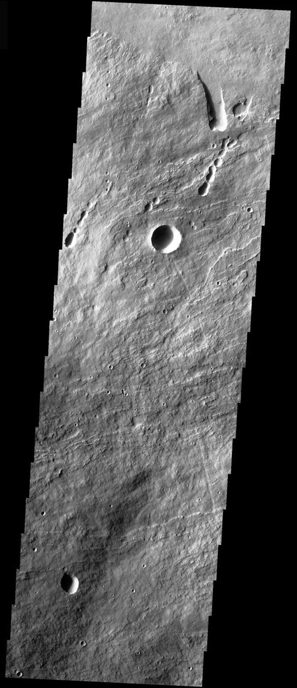 This image from NASA's Mars Odyssey spacecraft shows the part of the NE flank of Arsia Mons where it meets the plains. The flank of the volcano is comprised of long flows. Collapse features are present at the flank margin.