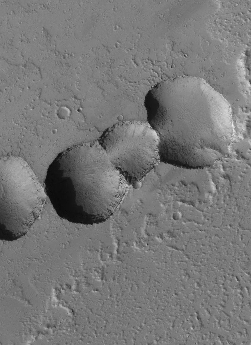 NASA's Mars Global Surveyor shows a chain of collapse pits fomed among dust-mantled lava flows in the eastern Tharsis region of Mars.