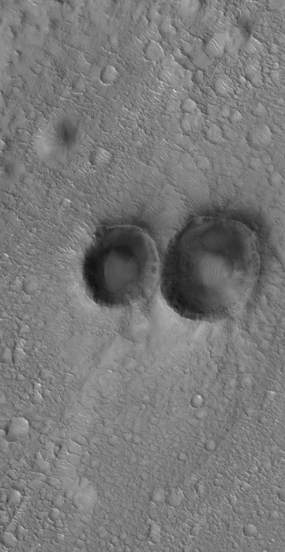 NASA's Mars Global Surveyor shows a pair of small meteor impact craters in the Arena Colles region of Mars, located north of Isidis Planitia.