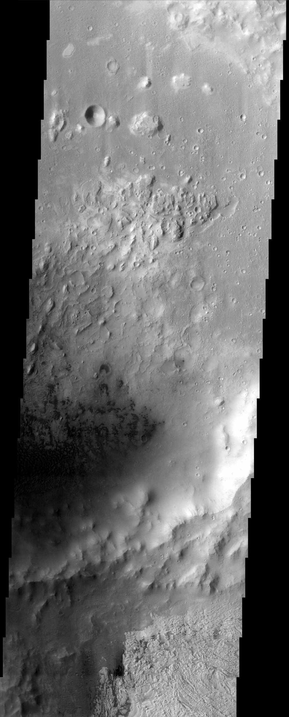 Dark dunes on the floor of an interior crater in Becquerel, imaged here by NASA's Mars Odyssey spacecraft, supply the sand responsible for the erosion of the remarkable, layered deposit to the south.