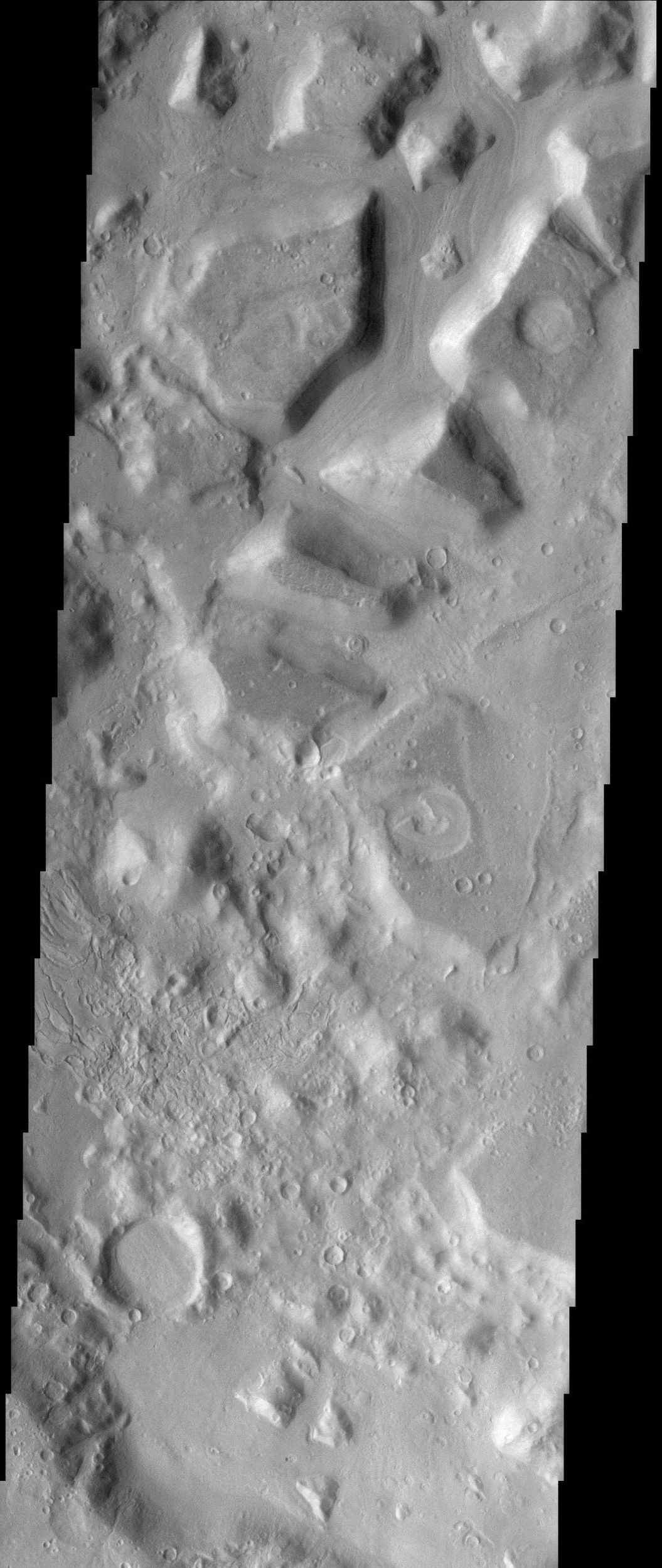 This NASA Mars Odyssey image shows the dissected interior of a crater in the Cydonia region of Mars. The flat-topped buttes and mesas in the northern portion of the image were once a continuous layer of material that filled the crater.