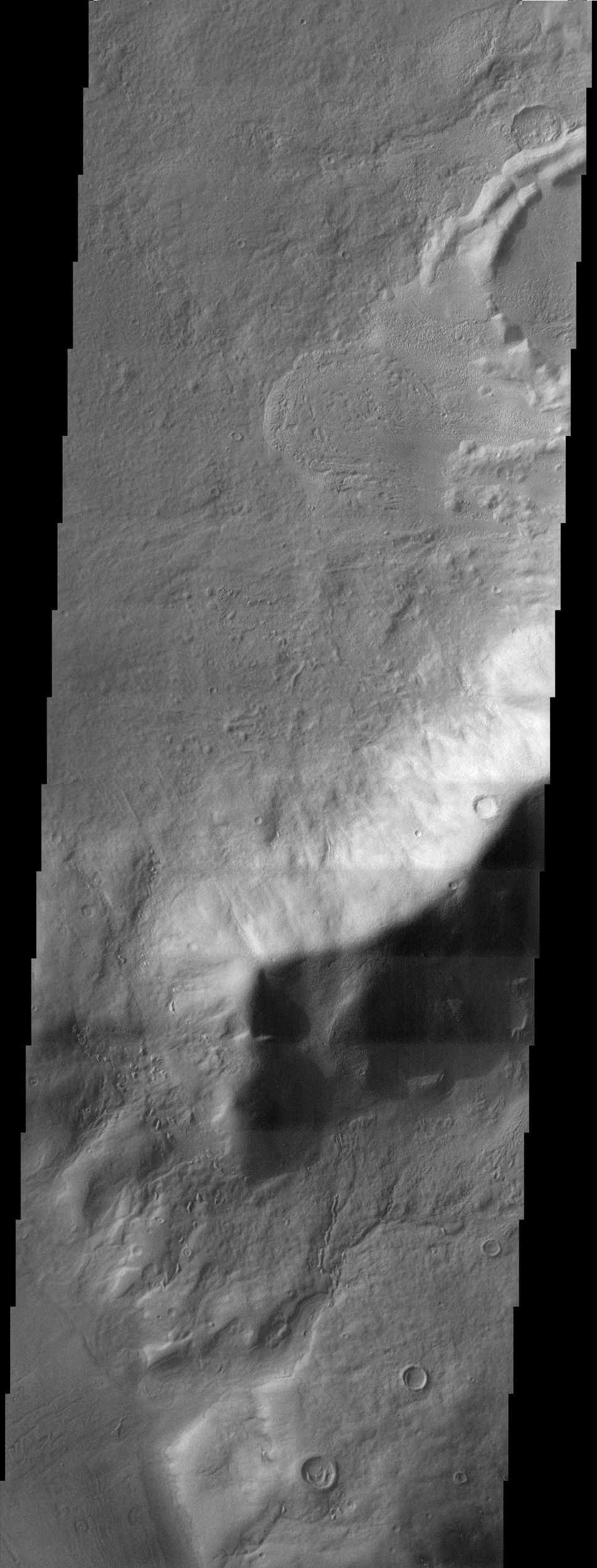 The channels and impact crater rim shown in this NASA Mars Odyssey image provide insight to the forces that have sculpted the surface within the extensive Reull Vallis network.