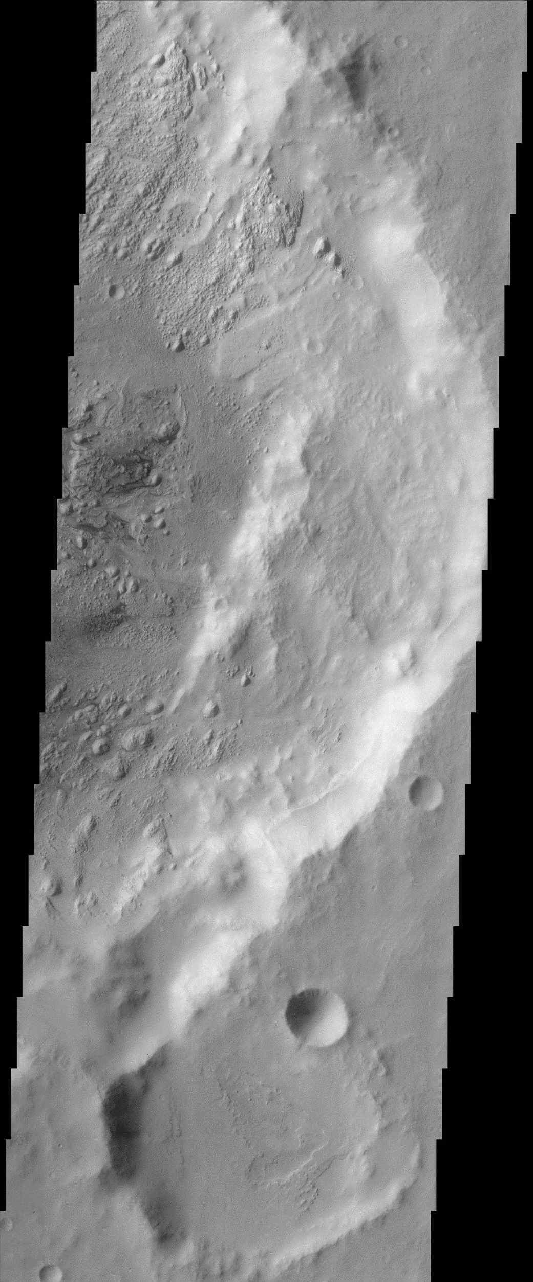 This image from NASA's Mars Odyssey covers a region in western Arabia Terra, which contains two interesting craters. The eastern floor of the largest crater seen in most of this image is bumpy and ridged in places and relatively smooth in regions.