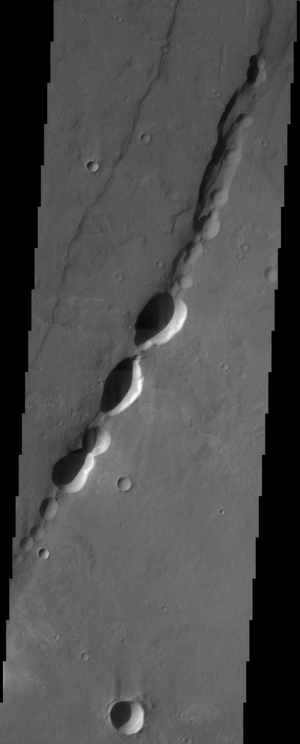 These pit-chain features in this NASA Mars Odyssey image of south Noctis Labryinthus are oriented parallel to grabens in the area, suggesting that tensional stresses may have been responsible for their formation.
