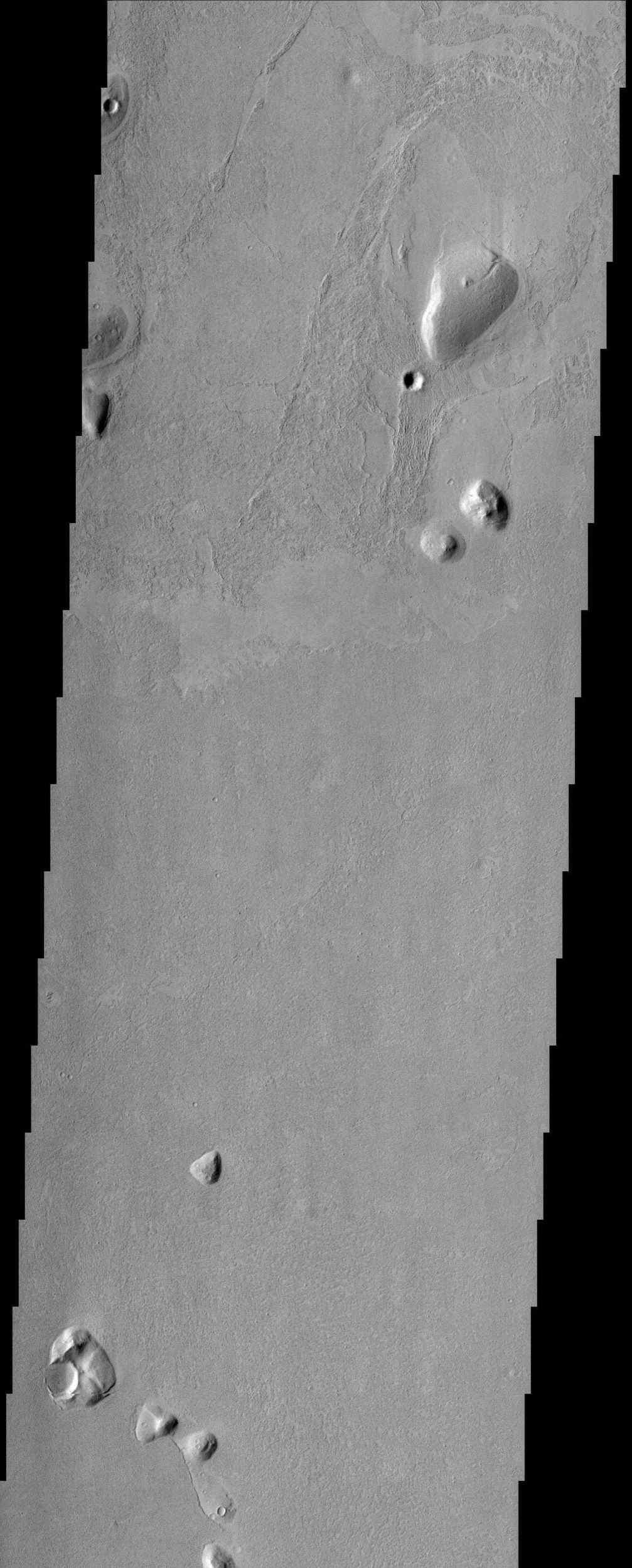 Islands of older high-standing terrain rise above a sea of relatively young, platy lava flows between two of the largest volcanoes in the solar system in this image from NASA's Mars Odyssey spacecraft.