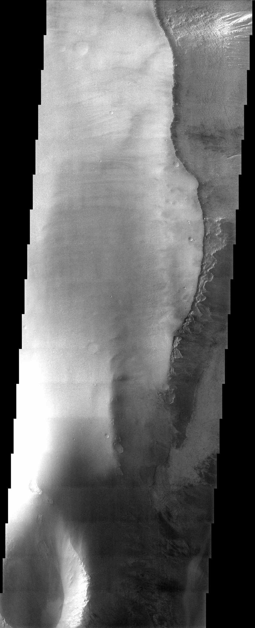In this image from NASA's Mars Odyssey, a mantling layer of sediment slumps off the edge of a mesa in Candor Chasma producing a ragged pattern of erosion that hints at the presence of a volatile component mixed in with the sediment.