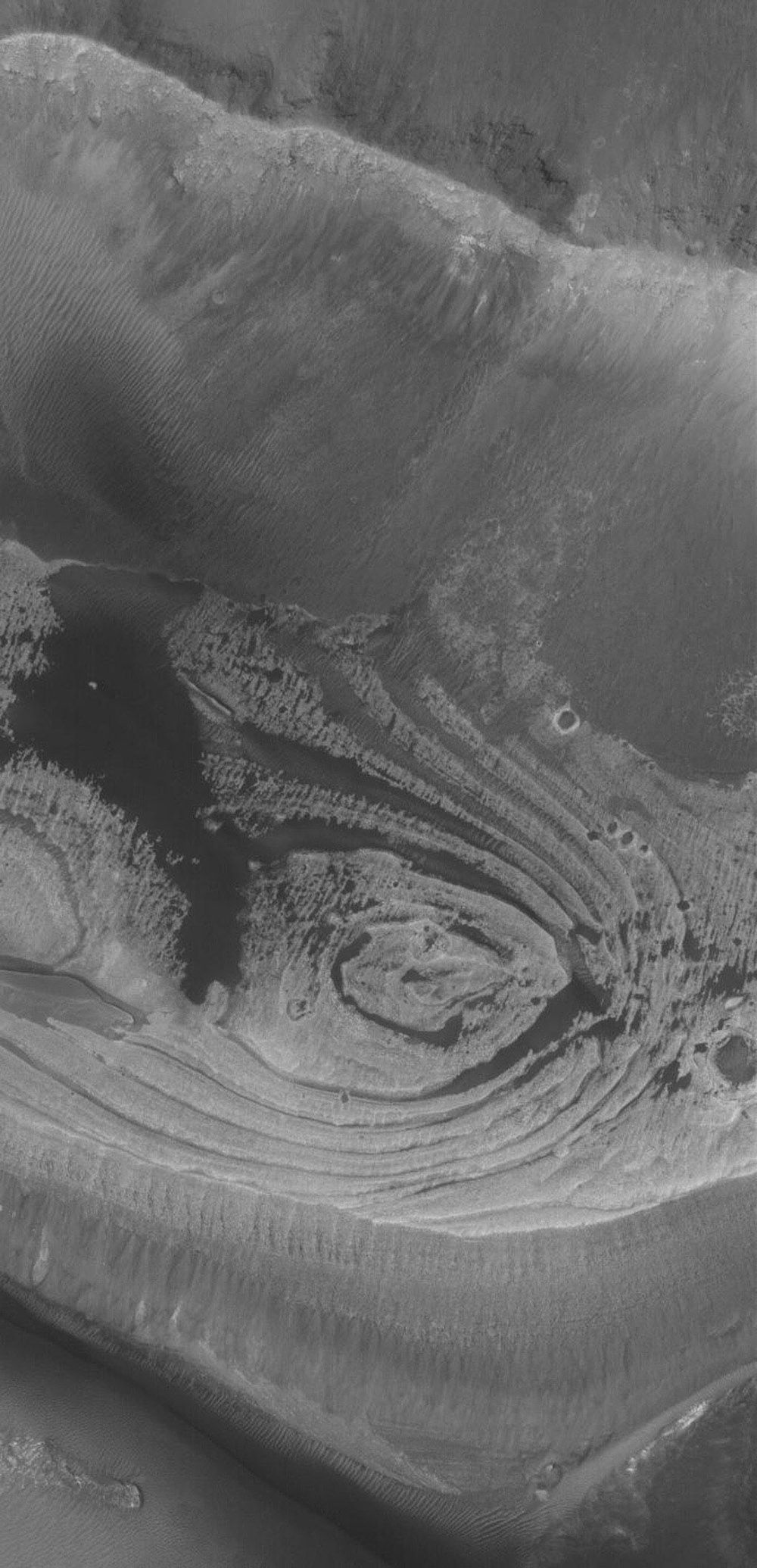 NASA's Mars Global Surveyor shows light-toned, layered rock outcrops found in eastern Candor Chasma, part of the vast Valles Marineris trough system on Mars.
