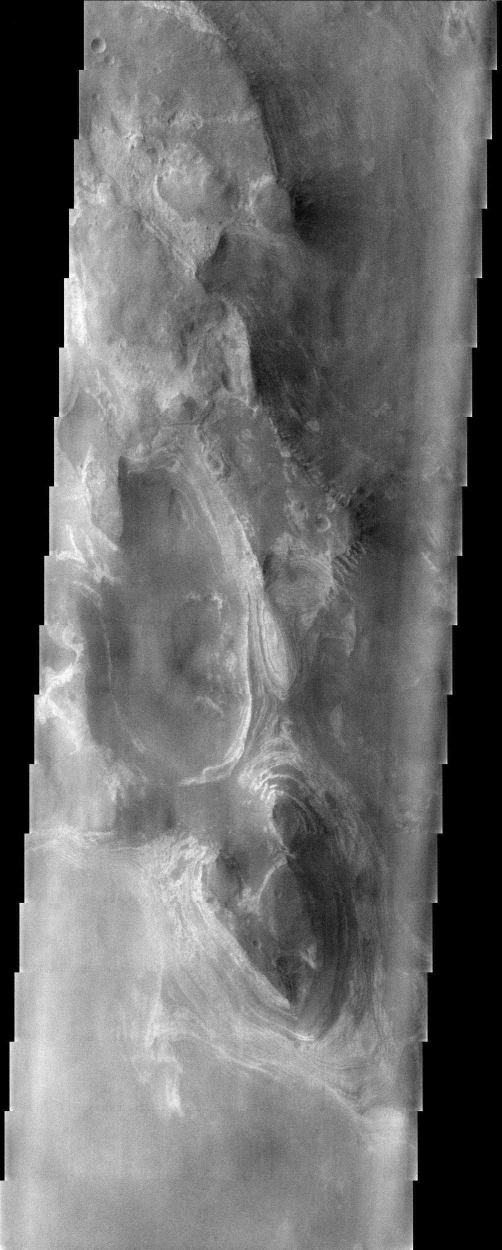 This somewhat cloudy image from NASA's Mars Odyssey spacecraft shows a stunning example of layered deposits in Terby crater, just north of the Hellas impact basin.