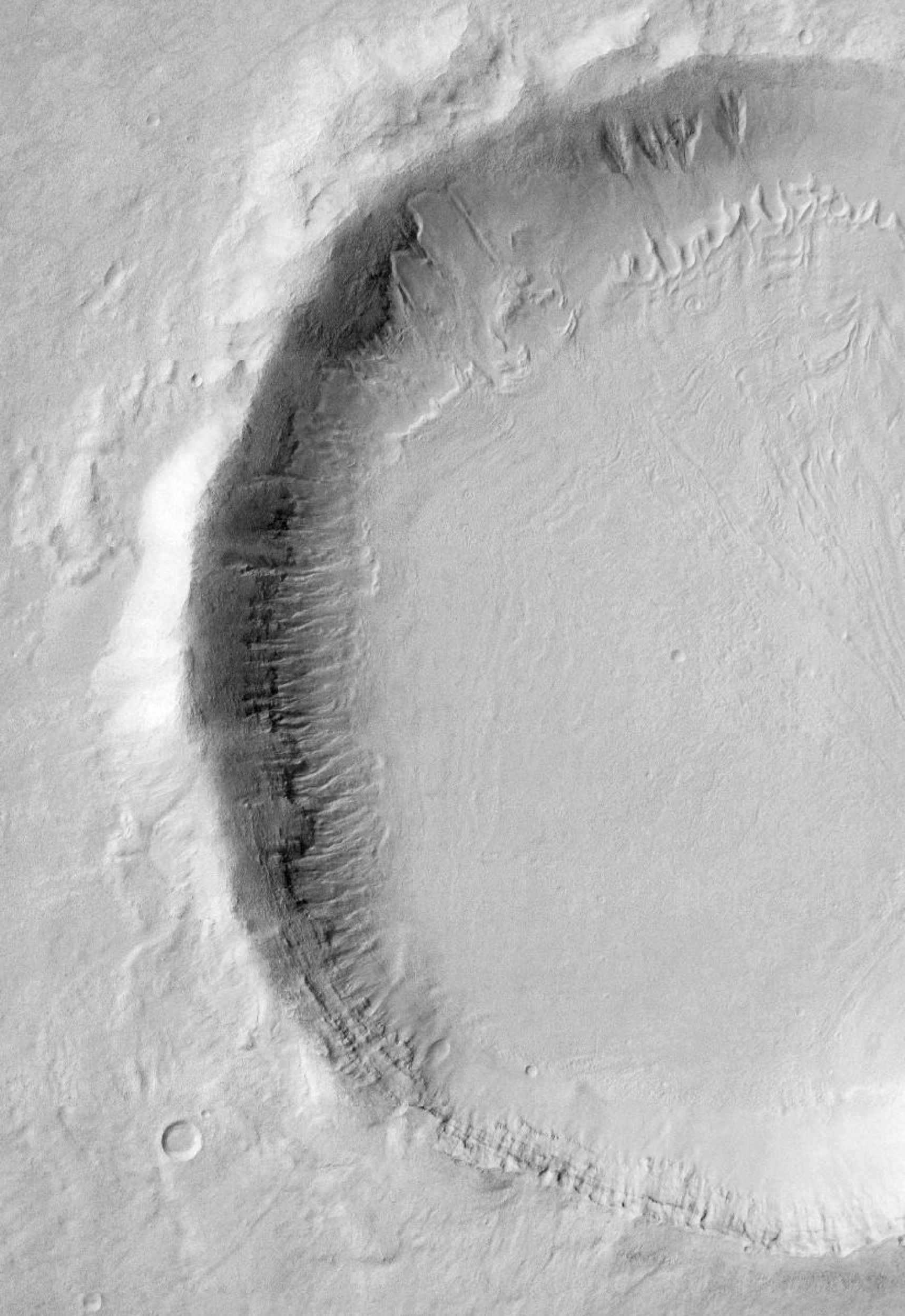 This visible-light image, taken by NASA's Mars Odyssey spacecraft, indicates that gullies on Martian crater walls may be carved by liquid water melting from remnant snow packs.