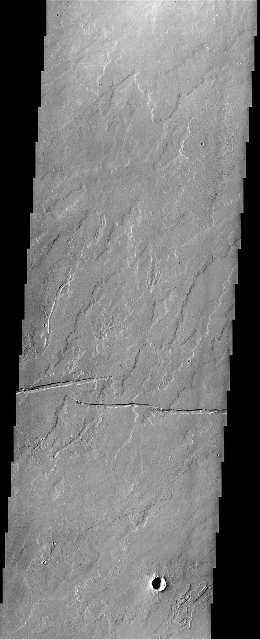 In this image from NASA's Mars Odyssey spacecraft, numerous lava flows and fossae (cracks) are visible in a region of Mars located southeast of Olympus Mons. There is also a hint that water may have possibly flowed in the region.