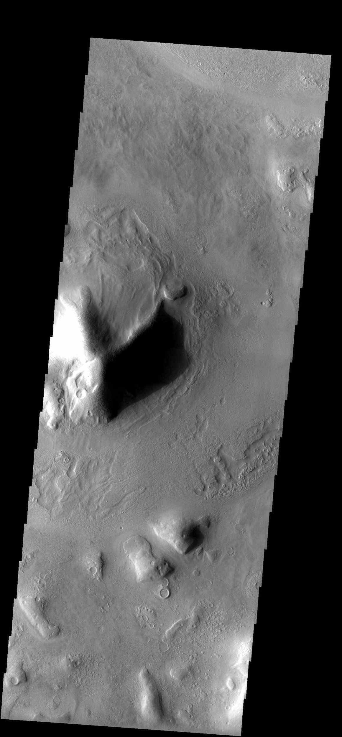 The mottled surface texture and flow features observed in this NASA Mars Odyssey image suggest materials may be, or have been, mixed with ice. There is also evidence in some areas for infilling of sediments as crater rims and ridges appear covered.
