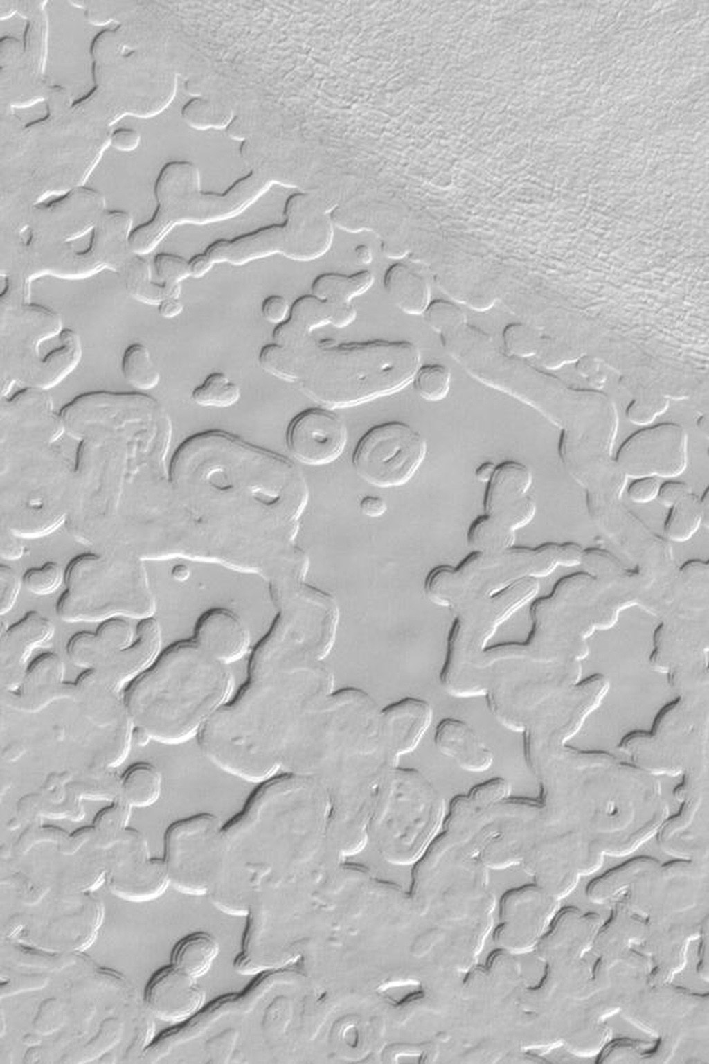 NASA's Mars Global Surveyor shows the 'swiss cheese' pattern of frozen carbon dioxide on the south polar residual cap.