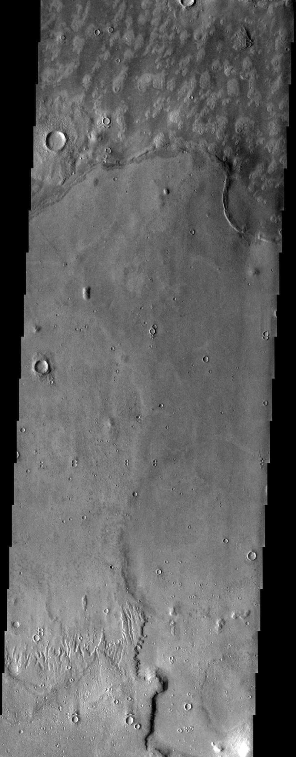 Embayment relationship is displayed where mottled plains material laps up against higher standing plains material in this image from NASA's Mars Odyssey spacecraft. The embaying material could be lava or possibly mud.