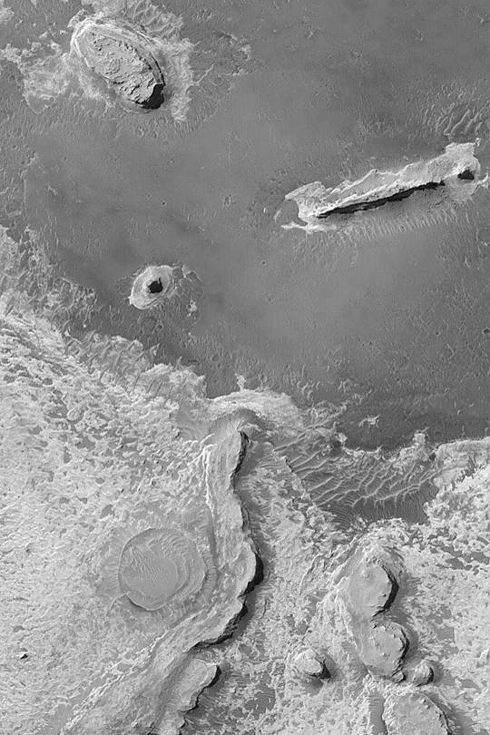 NASA's Mars Global Surveyor shows of layered sedimentary rock outcrops in northern Sinus Meridiani on Mars featuring several buttes and ridges formed in rock that is somewhat resistant to erosion.