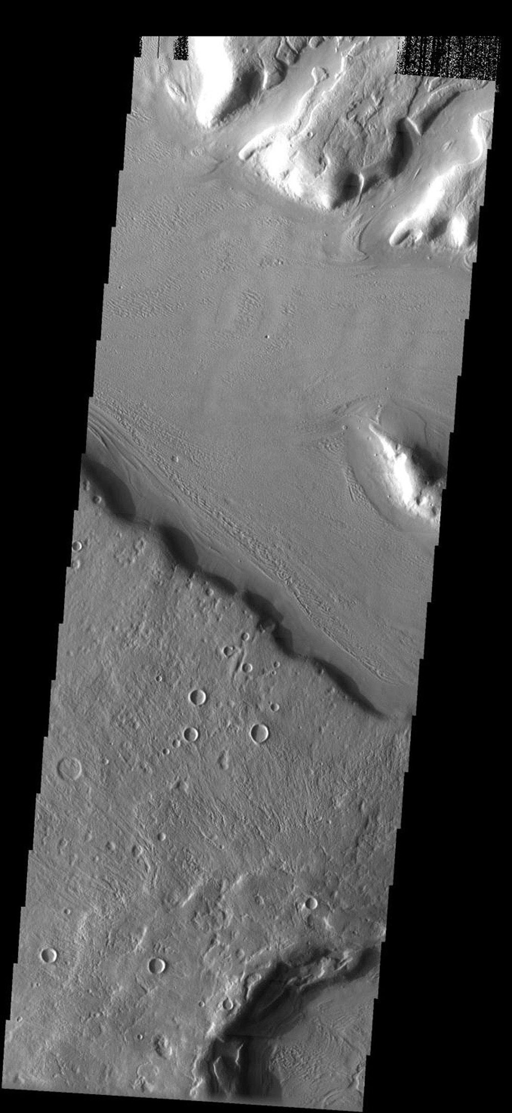 This image from NASA's Mars Odyssey shows lines indicative of flow in a valley floor on Mars cut across similar lines in a slightly smaller valley, indicating both that material flowed along the valley floor.
