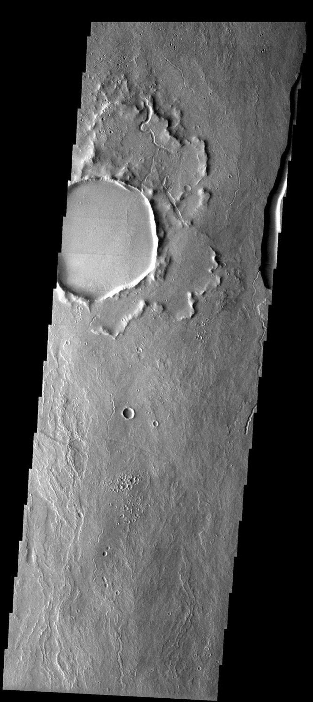 An unusual crater northeast of Ascraeus Mons on Mars displays an ejecta blanket that appears turned up around its edges, as seen in this image from NASA's Mars Odyssey.