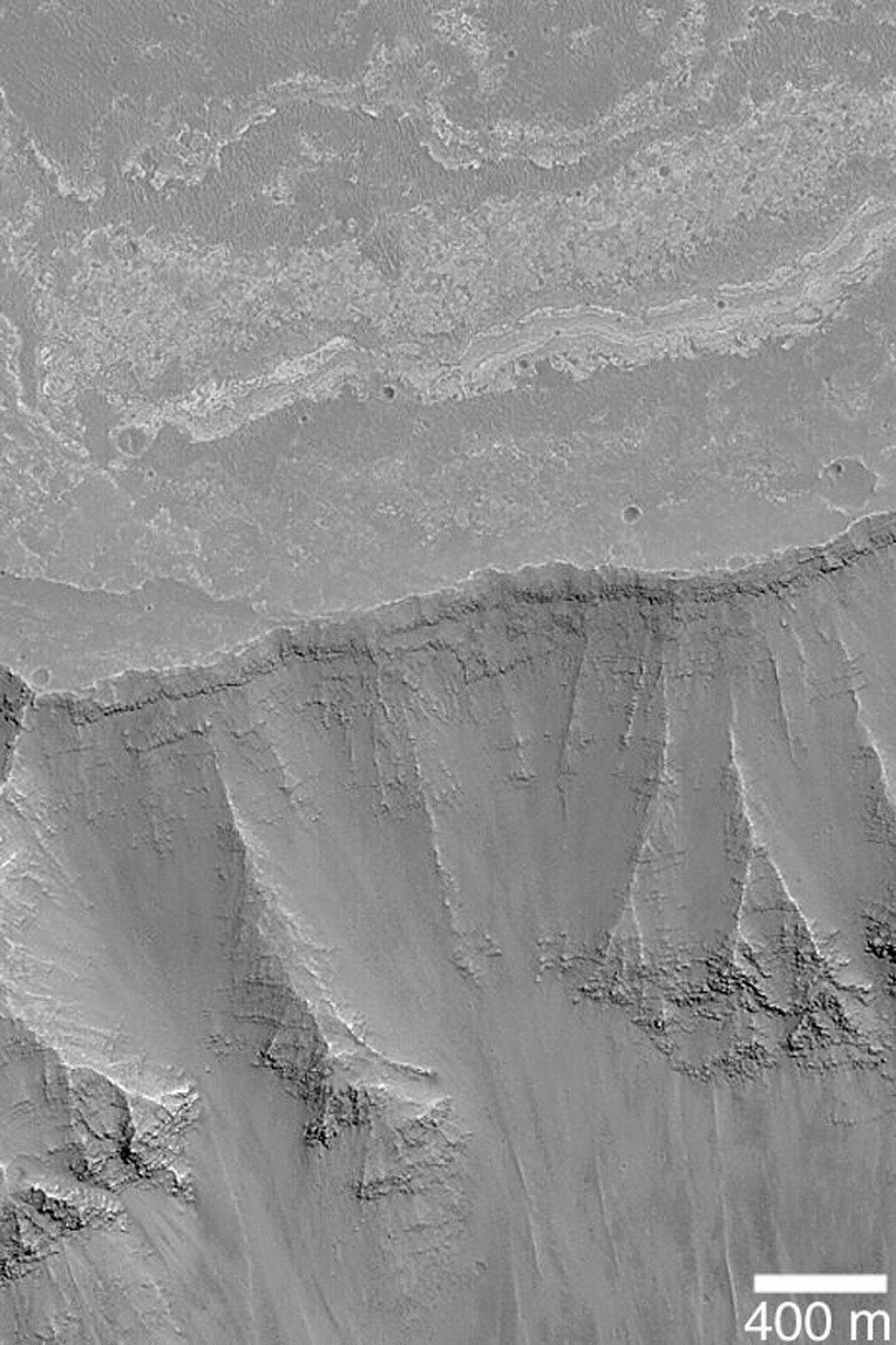 NASA's Mars Global Surveyor shows chasms and canyons cut through ancient, layered bedrock in West Candor, part of the vast Valles Marineris trough system on Mars.