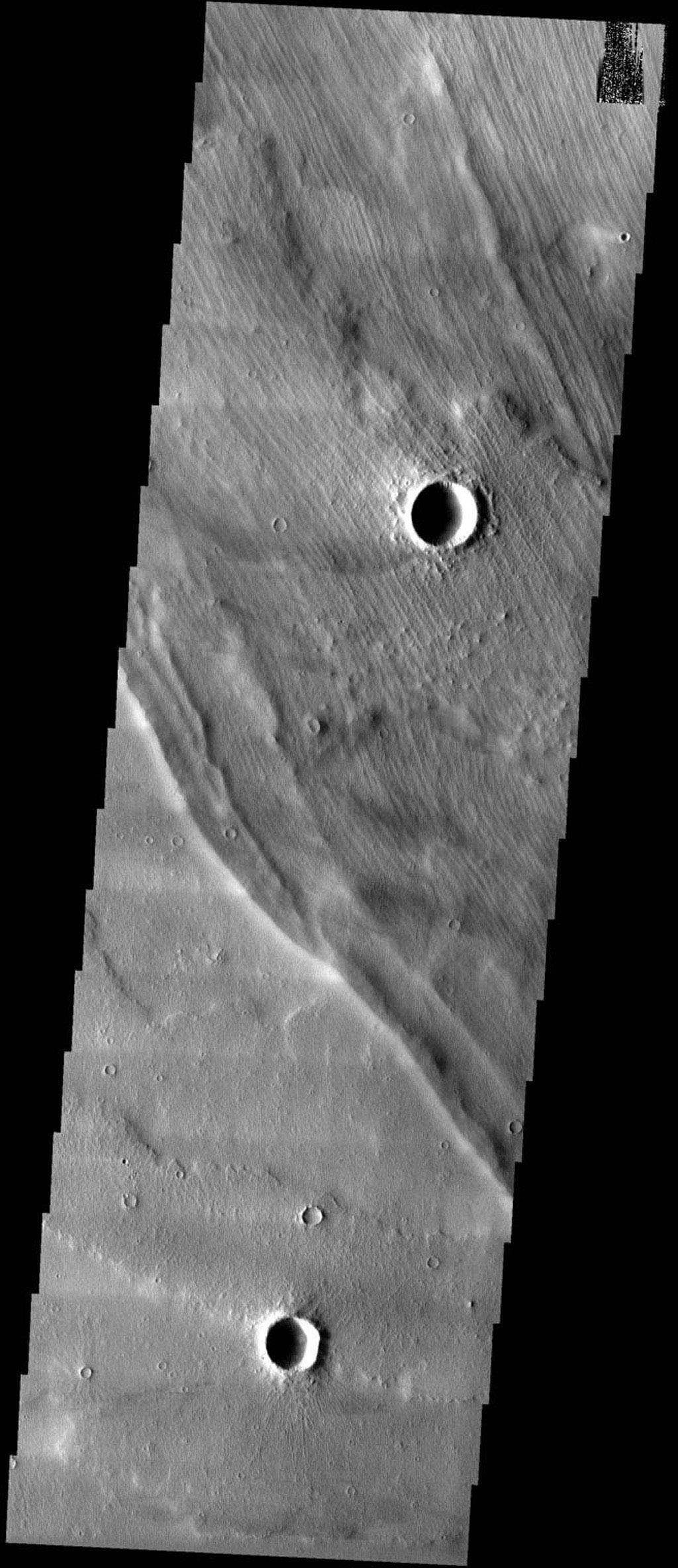 This image taken by NASA's 2001 Mars Odyssey shows strange-looking grooved terrain overlies lava flows off of the western flank of the giant shield volcano Arsia Mons on Mars.
