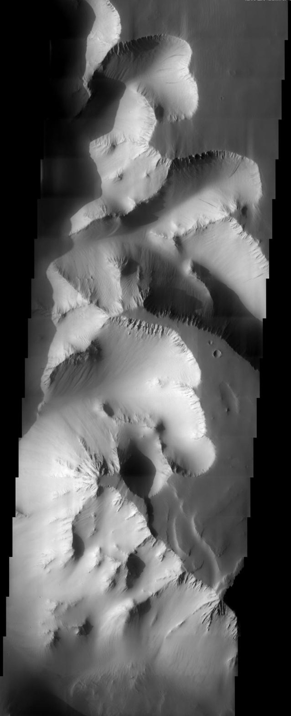 This image taken by NASA's 2001 Mars Odyssey shows high canyon walls of Valles Marineris on Mars. Geologic materials that are more resistant to erosion produce cliff forming units while landslides and streaks are observed on slope units.
