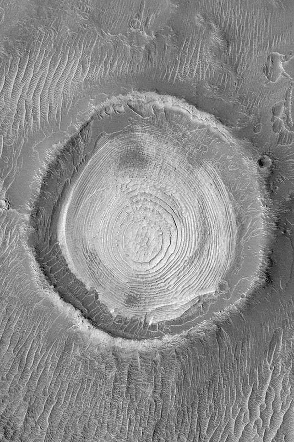 NASA's Mars Global Surveyor shows dozens of layers of similar thickness and physical properties in a wedding cake-like stack in the middle of an old meteor impact crater in northwestern Schiaparelli Basin on Mars.
