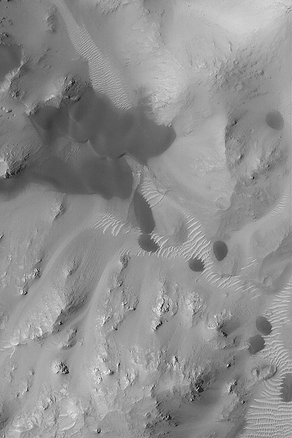 NASA's Mars Global Surveyor shows dark sand dunes and lighter-toned ripples trapped among the mountainous central peak of an old impact crater in Terra Tyrrhena on Mars.