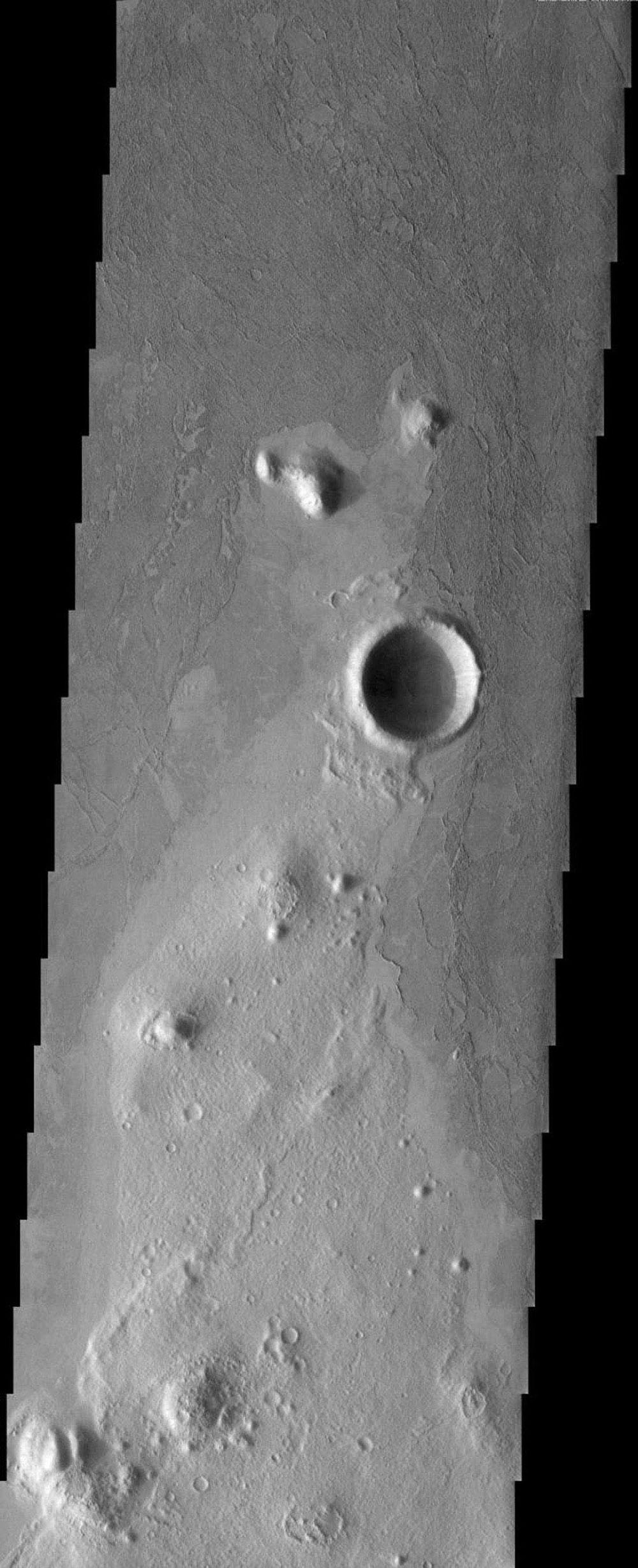 NASA's Mars Odyssey spacecraft captured this image in July 2003 of platy flows covering the plains of Southern Elysium on Mars. These flows appear to be very fluid lava flows but a mudflow origin can't be completely ruled out for these flows.