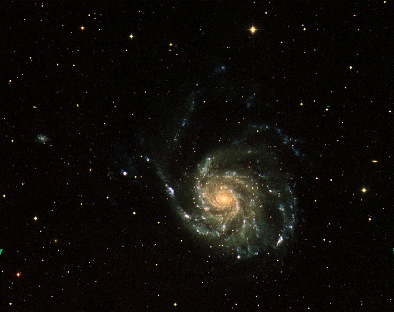 This three-color image of galaxy M101 was taken by NASA's Galaxy Evolution Explorer on June 20, 2003. The far ultraviolet emissions are shown in blue, the near ultraviolet emissions are green, and the red emissions, taken from NASA's Digital Sky Survey.