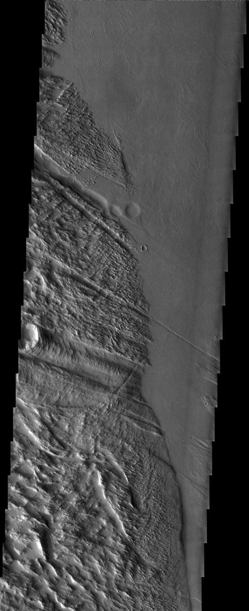 NASA's Mars Odyssey spacecraft captured this image in July 2003, roughly halfway between the great volcanoes of Olympus Mons and Pavonis Mons, the graben (troughs) of Ulysses Fossae intersect with the furrows of Gigas (gigantic) Sulci.