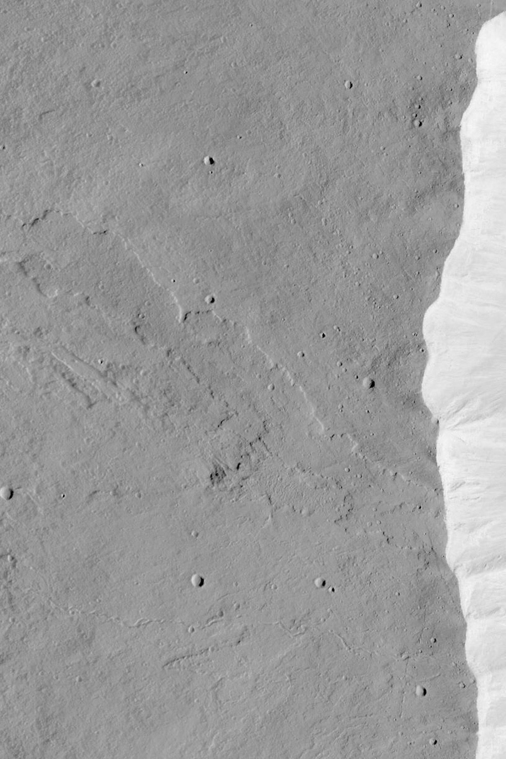 NASA's Mars Global Surveyor shows the western summit region of Olympus Mons on Mars featuring a lava flow that was cut by the pit walls when the caldera collapse occurred.
