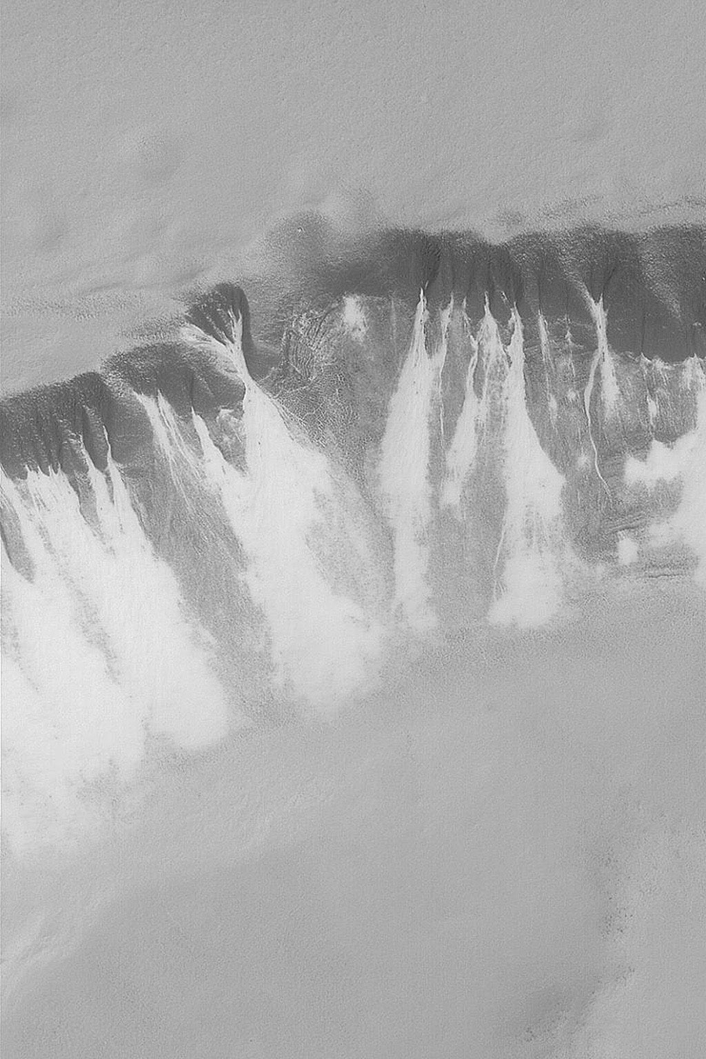 NASA's Mars Global Surveyor shows defrosting gullies and mass movement (landslide) features in the south polar region of Mars.