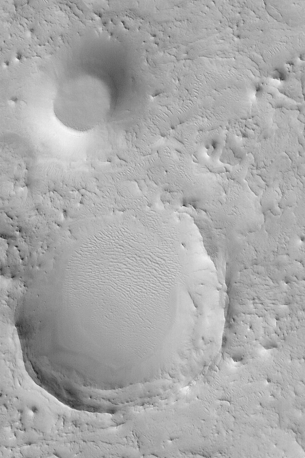 NASA's Mars Global Surveyor shows the remains of two former meteor impact craters in northeastern Arabia Terra on Mars.
