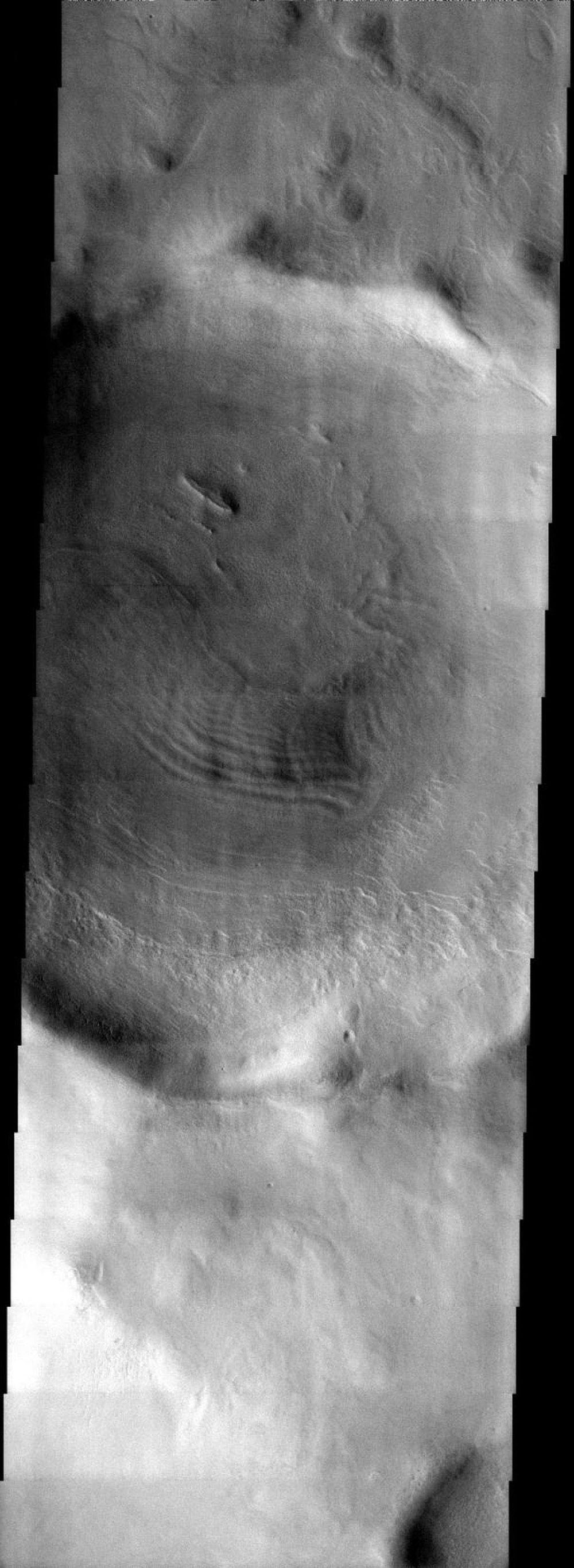 NASA's Mars Odyssey spacecraft captured this image in September 2003, showing a crater on Mars along the southeast rim of the Hellas Basin,hosting an eroded layered deposit like many of the neighboring craters.