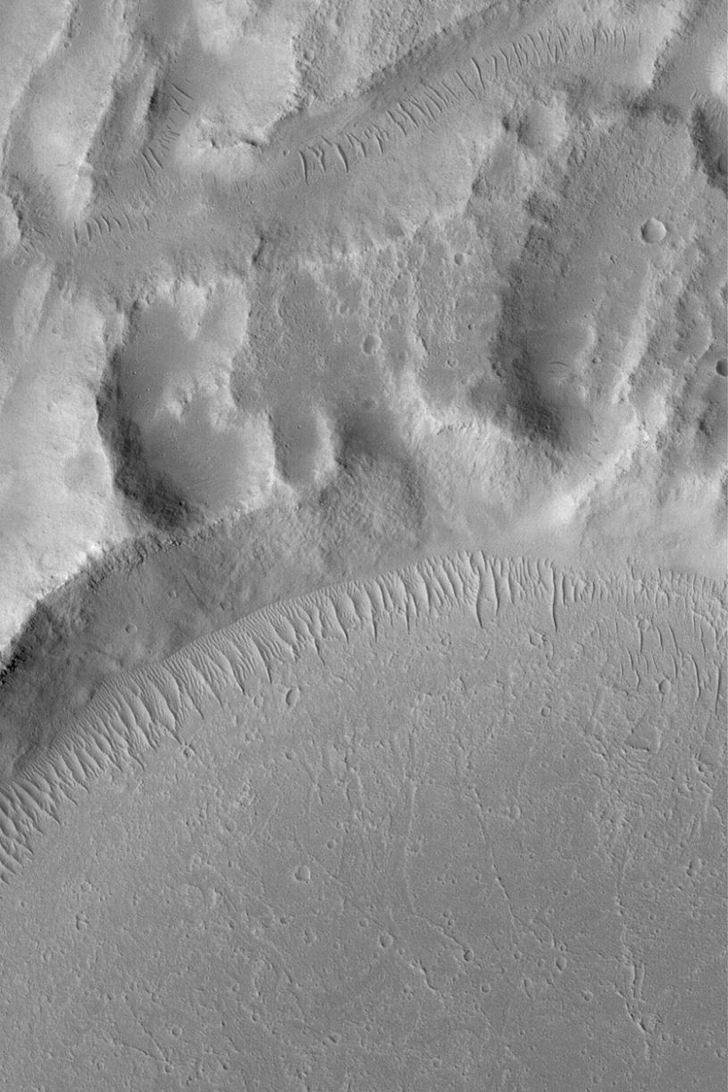 NASA's Mars Global Surveyor shows flow patterns formed by mud or lava from some of the youngest flow events that occurred in the terrain in the Kasei Valles region of Mars. Large, ripple-like, windblown bedforms are evident.