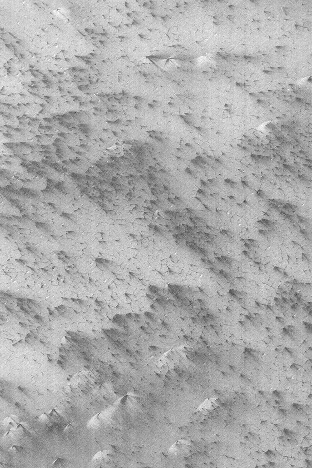 NASA's Mars Global Surveyor shows patterns created by defrosting processes on the martian south polar seasonal ice cap. Dark cracks form a polygon pattern, and wind blows material to form varied bright and dark streaks.