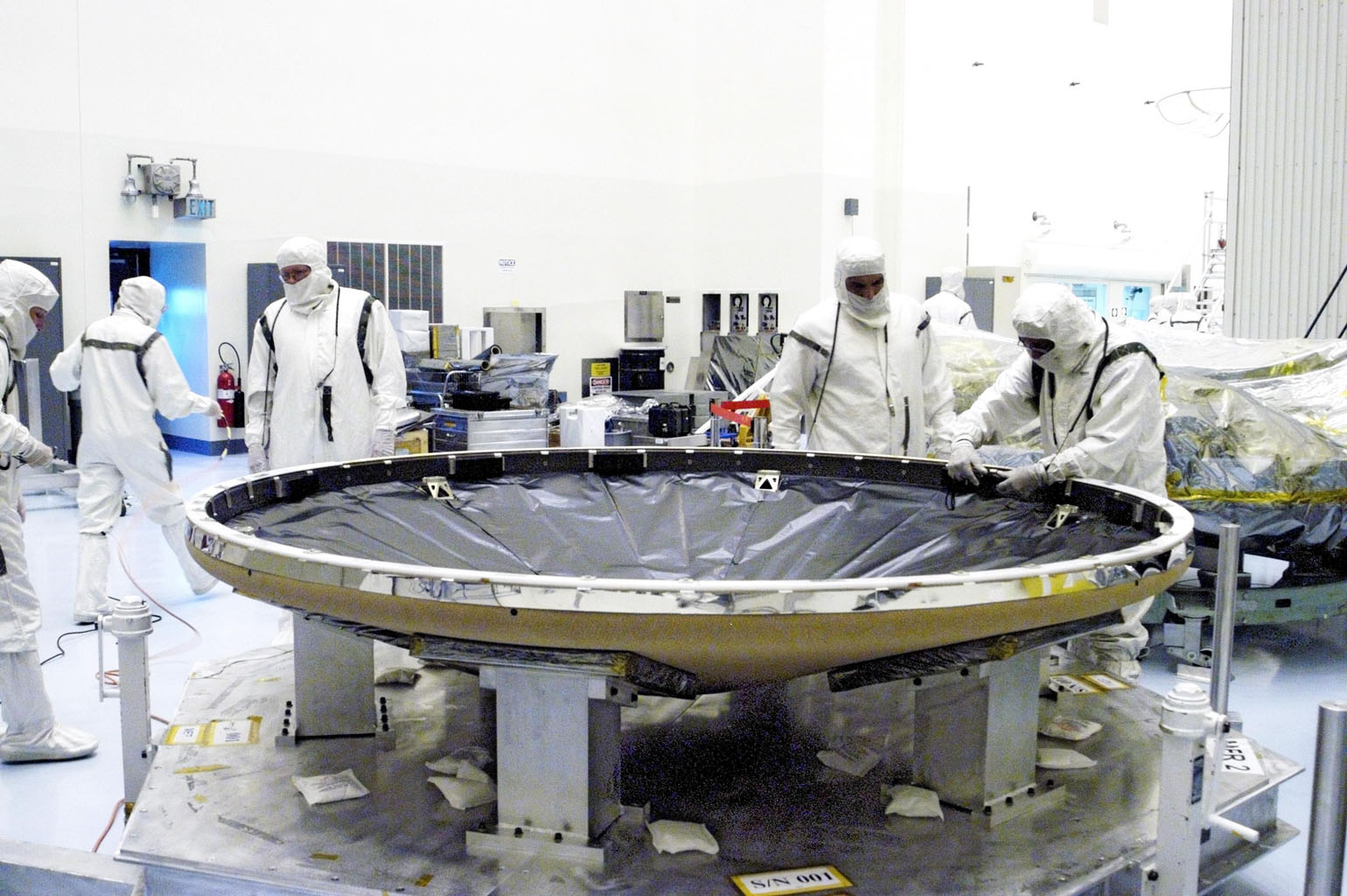 Workers in the Payload Hazardous Servicing Facility prepare the heat shield that will be attached to the backshell, surrounding Mars Exploration Rover 1 (MER-1).