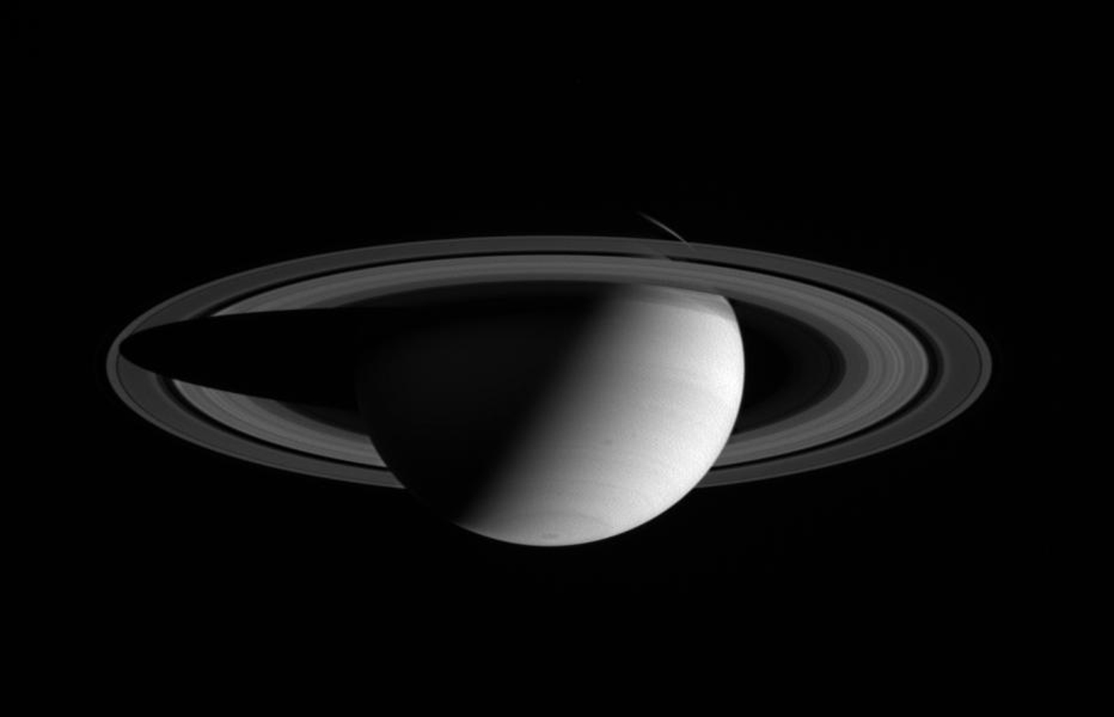 NASA's Cassini spacecraft wide angle camera view shows a half-lit Saturn, with two dark storms rolling through its southern hemisphere.
