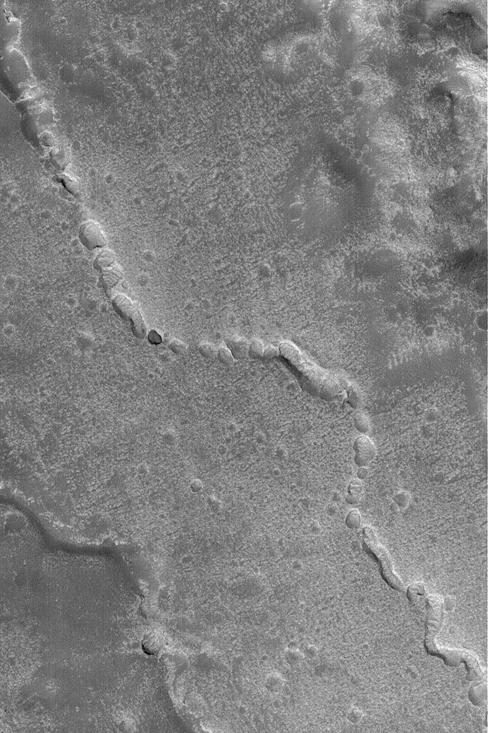 NASA's Mars Global Surveyor shows evidence of a collapsed lava tube (or other form of subterranean channel) on the plains northwest of the Elysium volcanoes on Mars.