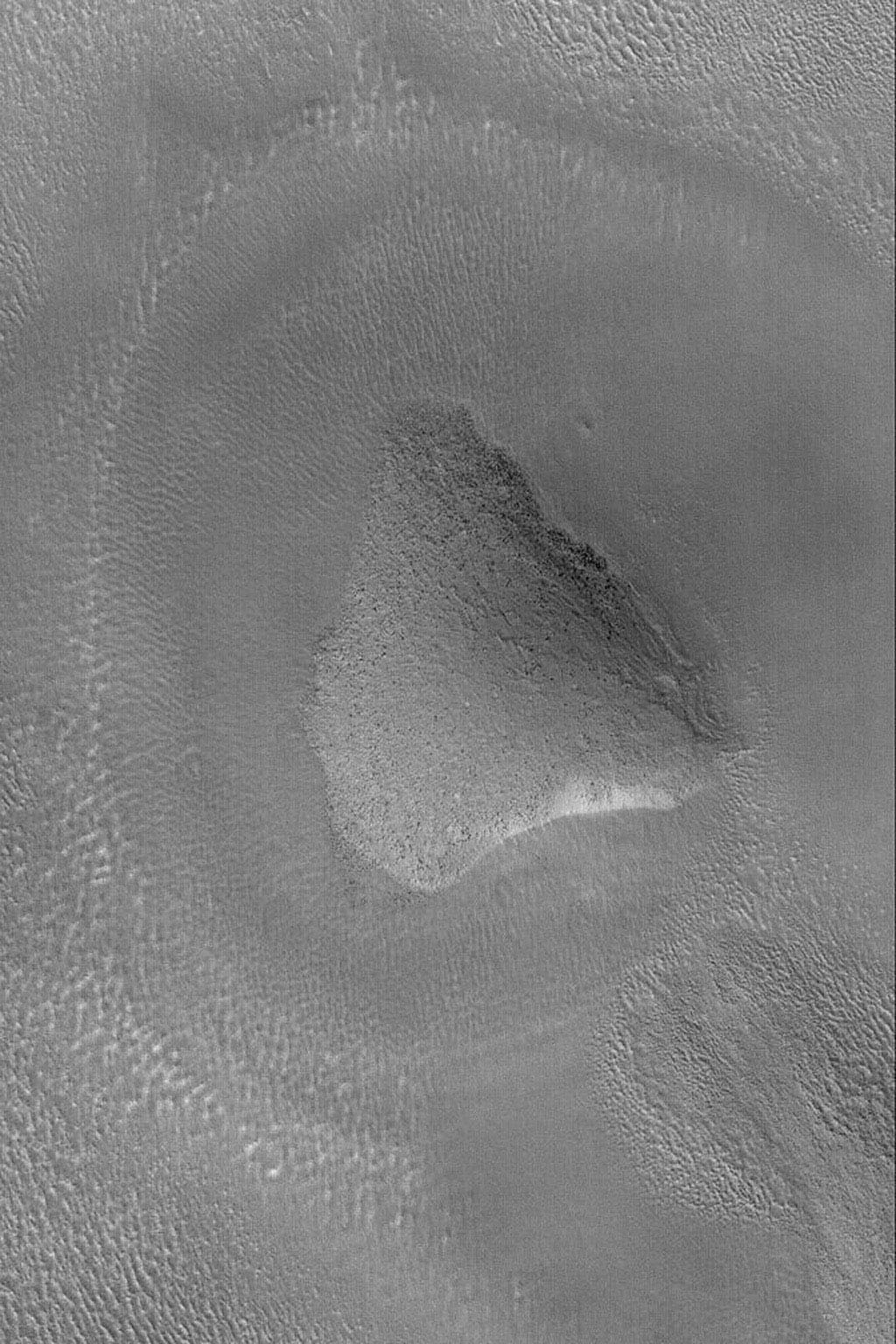 NASA's Mars Global Surveyor shows a rounded knob in the Propontis region of Mars. Dark dots on the hilltop and slopes are house-sized (and larger) boulders.